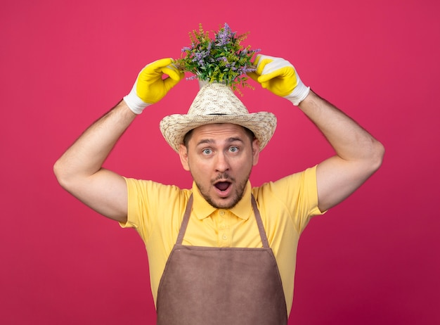 Jonge tuinman die een jumpsuit en een hoed in werkhandschoenen draagt die een potplant boven zijn hoofd houdt en verbaasd en verrast kijkt terwijl hij over de roze muur staat