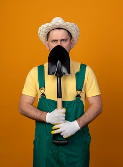 Jonge tuinman die in jumpsuit en de schop van de hoedenholding voorzijde met ernstig gezicht bekijken die zich over oranje muur bevinden