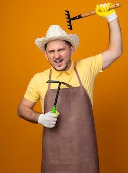 Jonge tuinman die jumpsuit en hoed draagt die houweel houdt die een hark slingert die voorzijde met boos gezicht bekijkt dat zich over oranje muur bevindt