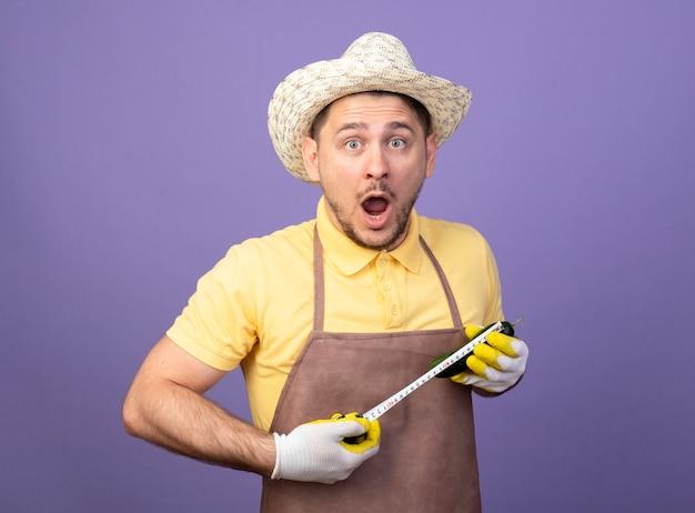 Jonge tuinman die jumpsuit en hoed in werkhandschoenen draagt die aubergine houdt die het meet met meetlint kijkt verbaasd status over purpere muur