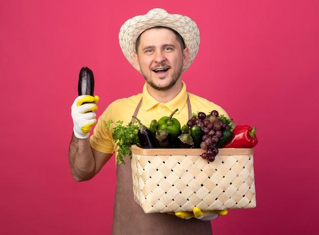 Jonge tuinman die jumpsuit en hoed in werkhandschoenen draagt die een krat vol groenten houdt die verse aubergine toont die aan de voorkant glimlachen, blij en positief staat over roze muur