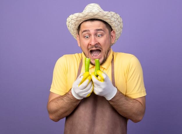 Jonge tuinman die jumpsuit en hoed in werkhandschoenen draagt die gebroken groene spaanse peperpeper houdt die het bekijkt wordt geschokt status over purpere muur