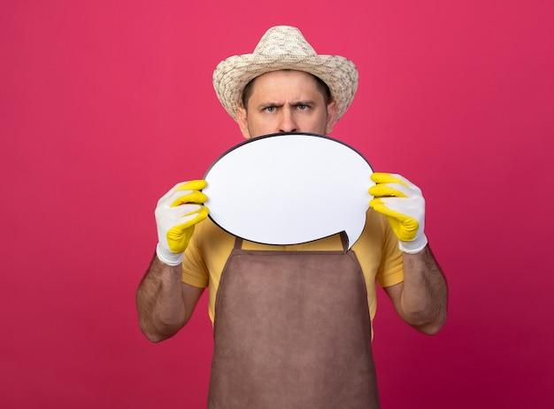 Jonge tuinman die jumpsuit en hoed in werkhandschoenen draagt die leeg teken van de toespraakbel houdt die voorzijde met ernstig gezicht bekijkt dat zich over roze muur bevindt