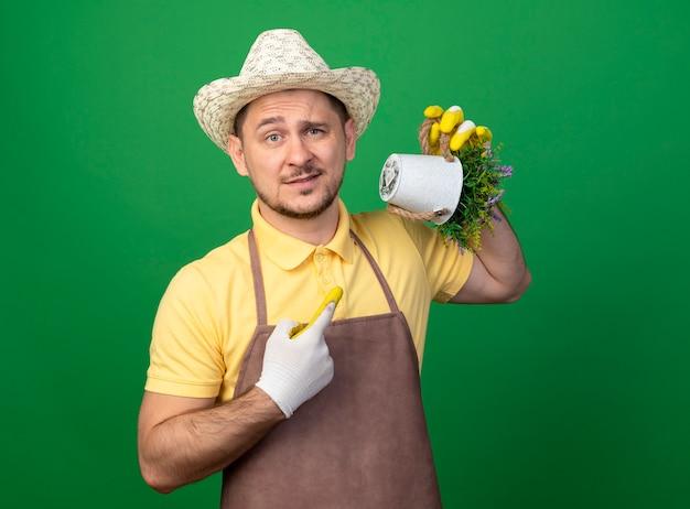 Jonge tuinman die jumpsuit en hoed in werkhandschoenen draagt die potplant houdt die met wijsvinger ernaar richt en met sceptische glimlach over groene muur kijkt