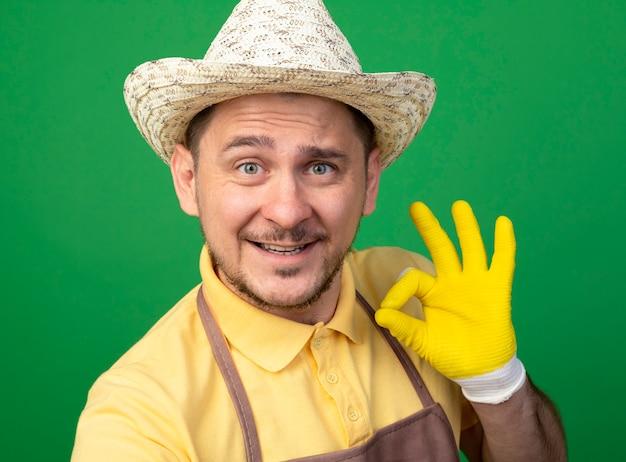 Jonge tuinman die jumpsuit en hoed in werkhandschoenen draagt die voorzijde bekijkt die ok teken toont glimlachend vrolijk status over groene muur