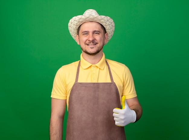 Jonge tuinman die jumpsuit en hoed in werkhandschoenen draagt die voorzijde het glimlachen bekijkt die duimen toont die zich over groene muur bevinden