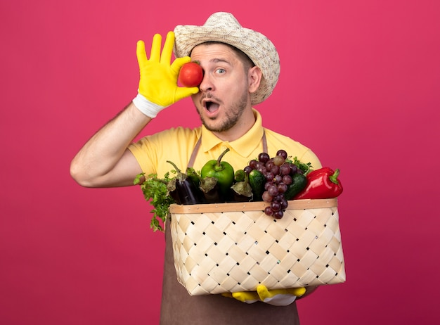 Jonge tuinman die jumpsuit en hoed in werkhandschoenen draagt en een krat vol groenten en verse tomaat boven zijn oog houdt en verbaasd over roze muur kijkt