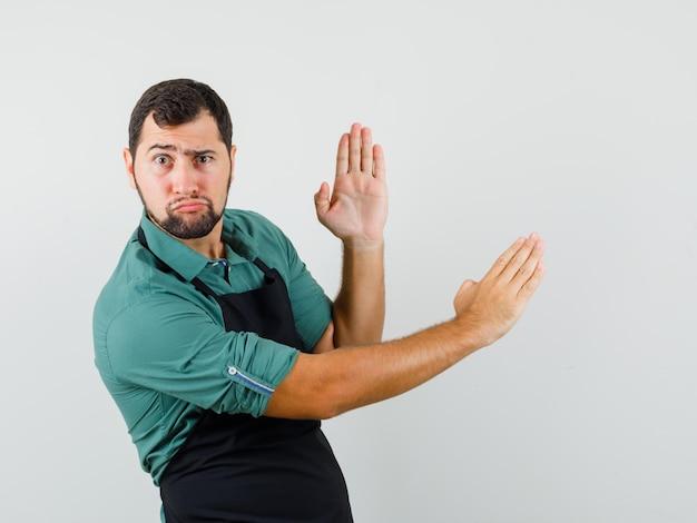 Jonge tuinman die karatekarbonade in t-shirt, schort toont en er snel uitziet. vooraanzicht.