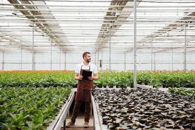 Jonge tuinman die met installaties in serre werkt