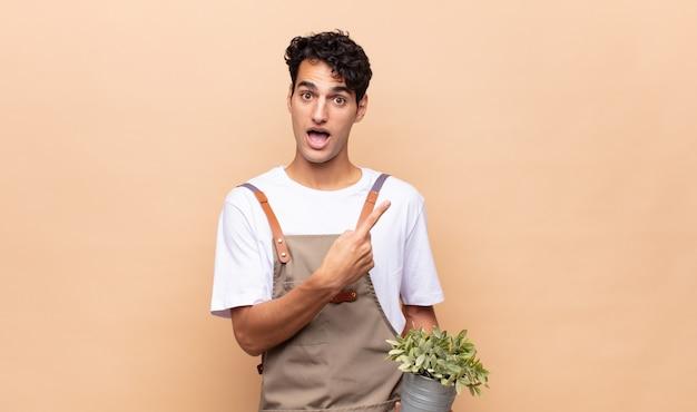 Jonge tuinman die opgewonden en verrast kijkt en naar de zijkant en naar boven wijst om ruimte te kopiëren