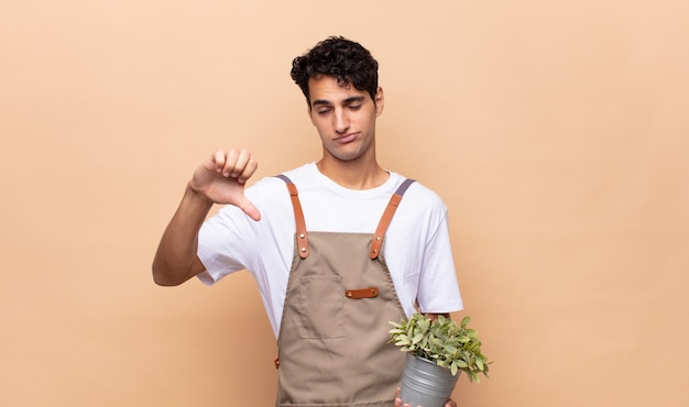Jonge tuinman die zich boos, boos, geïrriteerd, teleurgesteld of ontevreden voelt, duimen naar beneden met een serieuze blik