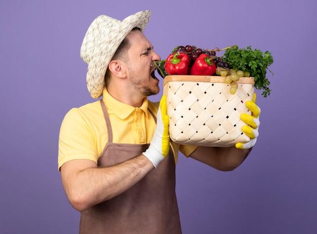 Jonge tuinman dragen jumpsuit en hoed in werkhandschoenen bedrijf krat vol groenten gaan bijten groenten staande over paarse muur