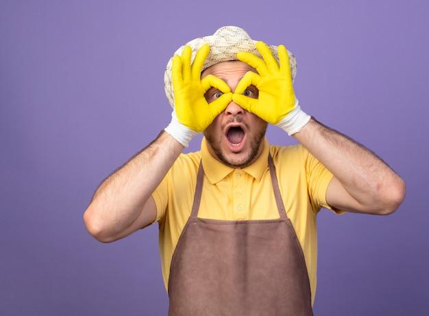 Jonge tuinman dragen jumpsuit en hoed in werkhandschoenen verrekijker gebaar maken met vingers kijken door vingers kijken verbaasd staande over paarse muur