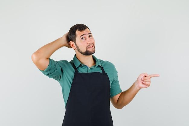 Jonge tuinman houdt hand op zijn hoofd terwijl hij opzij wijst in t-shirt, schort en verbaasd vooraanzicht kijkt