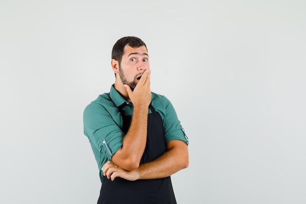 Jonge tuinman houdt hand op zijn mond in t-shirt, schort en kijkt verrast, vooraanzicht.