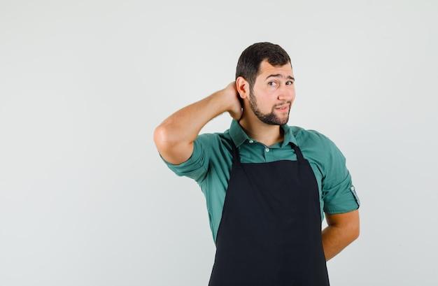 Jonge tuinman houdt hand op zijn nek in t-shirt, schort en ziet er aantrekkelijk uit, vooraanzicht.