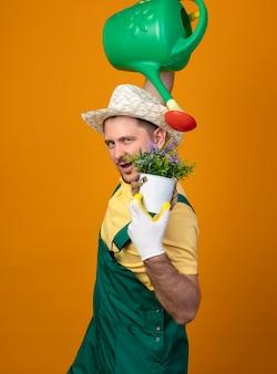 Jonge tuinman in jumpsuit en hoed met gieter en potplant blij en positief glimlachend vrolijk staande over oranje muur