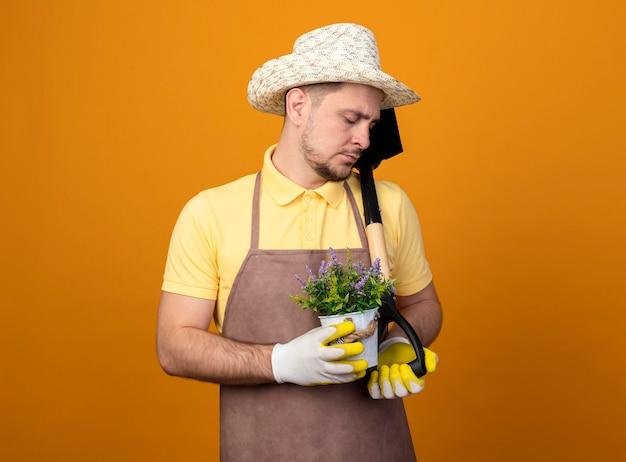 Jonge tuinman in jumpsuit en hoed met schop en potplant neerkijkt met droevige uitdrukking staande over oranje muur