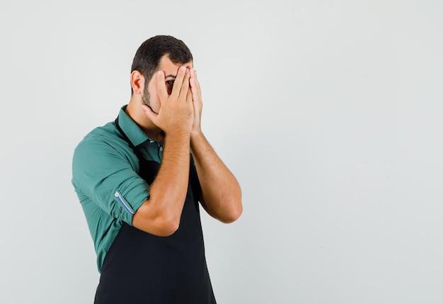 Jonge tuinman in t-shirt, schort die door zijn vingers kijkt en bang kijkt, vooraanzicht. vrije ruimte voor uw tekst