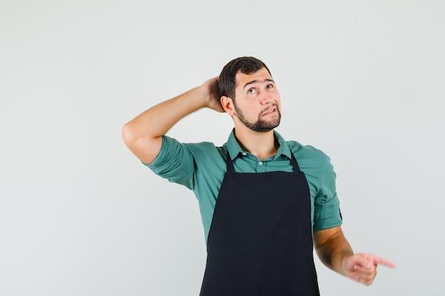 Jonge tuinman in t-shirt, schort die hand op zijn hoofd houdt terwijl hij opzij wijst en verbaasd kijkt, vooraanzicht.