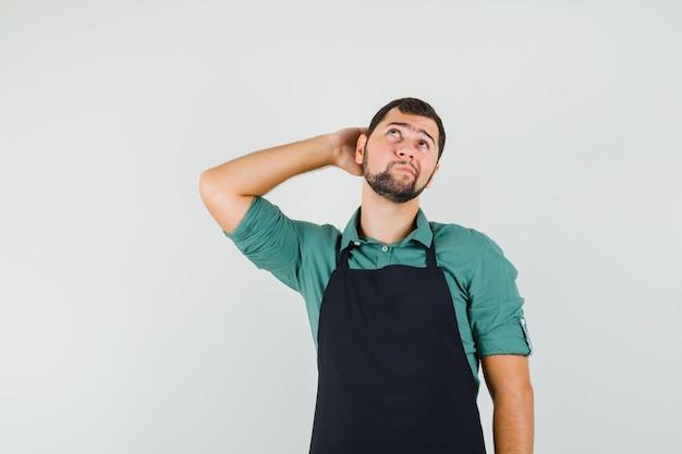 Jonge tuinman in t-shirt, schort die hand op zijn nek houdt en peinzend kijkt, vooraanzicht.