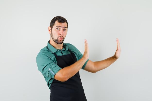 Jonge tuinman in t-shirt, schort die handen op een beschermende manier opheft, vooraanzicht.