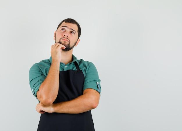 Jonge tuinman in t-shirt, schort leunend op zijn kaak terwijl hij omhoog kijkt en peinzend kijkt, vooraanzicht. ruimte voor tekst