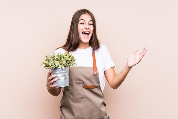 Jonge tuinman kaukasische vrouw die een geïsoleerde plant houdt die een aangename verrassing ontvangt, opgewekt en handen opheft.