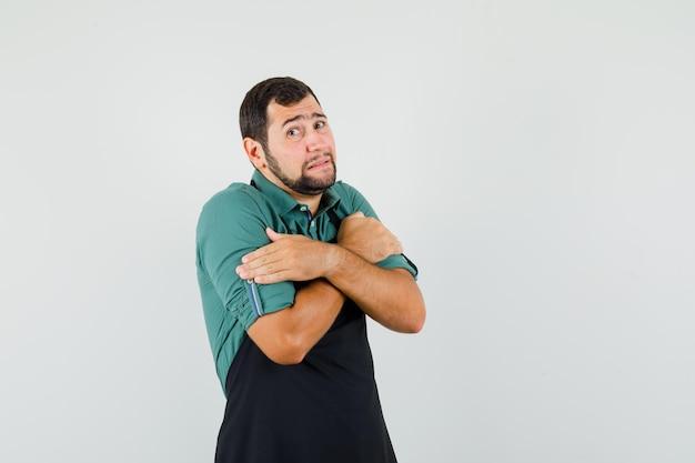 Jonge tuinman knuffelt zichzelf in t-shirt, schort en ziet er kil uit, vooraanzicht.