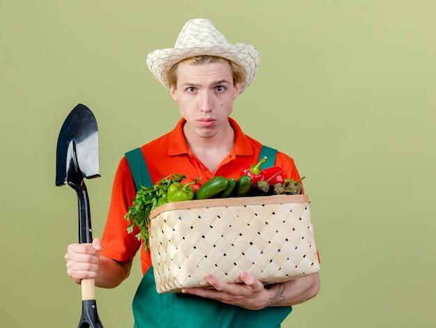 Jonge tuinman man dragen jumpsuit en hoed bedrijf krat vol groenten en schop camera kijken met ernstig gezicht staande over lichte achtergrond