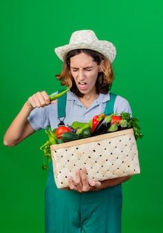 Jonge tuinman man dragen jumpsuit en hoed bedrijf krat vol verse groenten