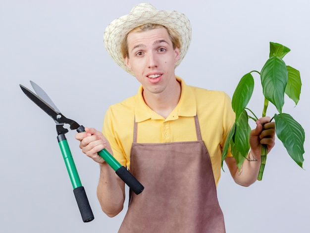 Jonge tuinman man dragen jumpsuit en hoed bedrijf plant en heggenschaar kijken camera lachend met blij gezicht staande op witte achtergrond