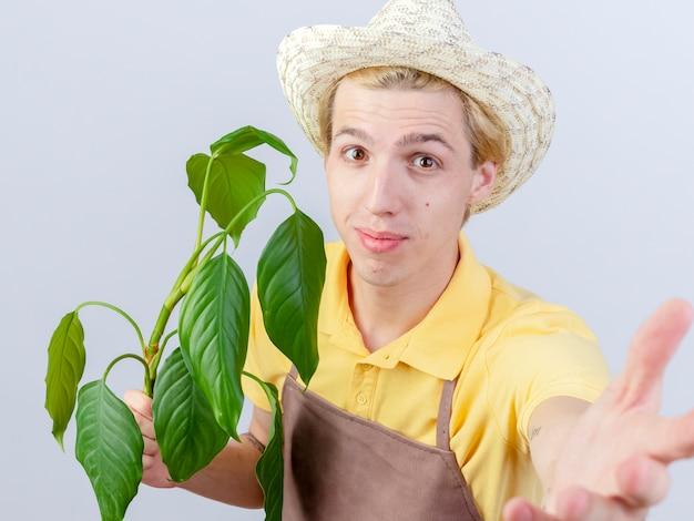 Jonge tuinman man dragen jumpsuit en hoed bedrijf plant kijken camera lachend met blij gezicht staande op witte achtergrond
