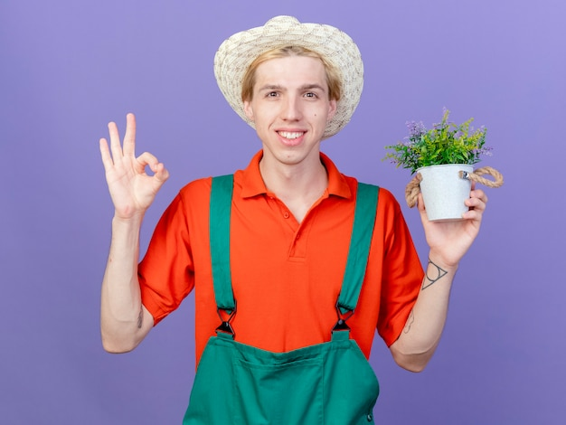 Jonge tuinman man dragen jumpsuit en hoed bedrijf potplant glimlachen