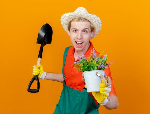 Jonge tuinman man dragen jumpsuit en hoed bedrijf schop weergegeven: potplant kijken camera glimlachend vrolijk met blij gezicht staande over oranje achtergrond