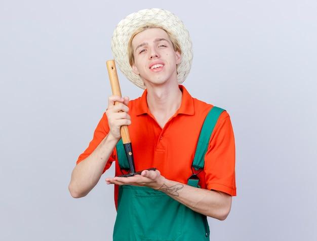 Jonge tuinman man dragen jumpsuit en hoed demonstreren mini hark kijken camera glimlachend zelfverzekerd staande op witte achtergrond