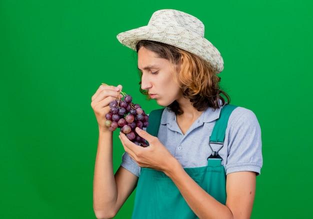 Jonge tuinman man dragen jumpsuit en hoed houden bos van druiven kijken ernaar