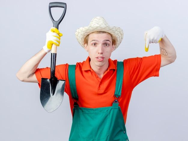 Jonge tuinman man dragen jumpsuit en hoed in rubberen handschoenen houden schop kijken camera wijzend met index figner naar beneden staande op witte achtergrond
