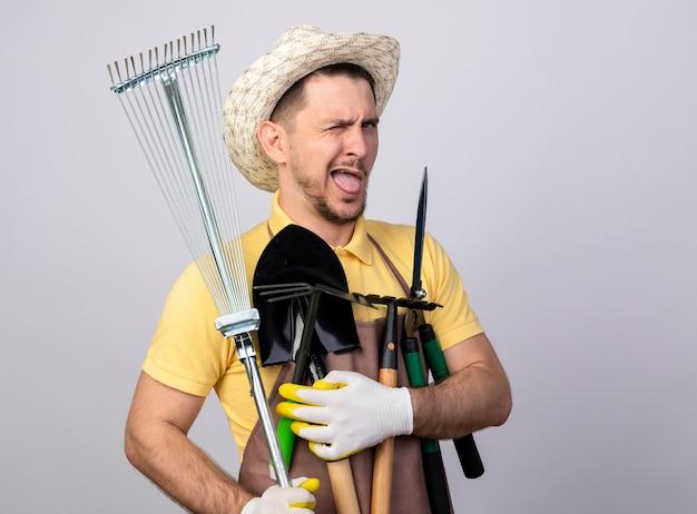 Jonge tuinman man dragen jumpsuit en hoed in werkhandschoenen houden tuinieren apparatuur glimlachend en knipogen tong uitsteekt