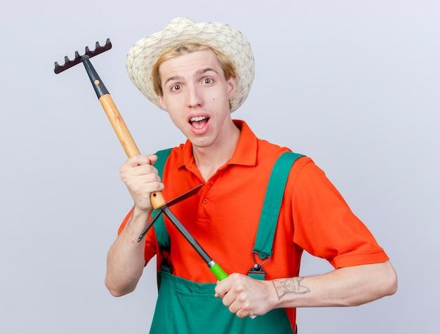 Jonge tuinman man dragen jumpsuit en hoed met mini hark en houweel kijken camera met glimlach op gezicht staande op witte achtergrond