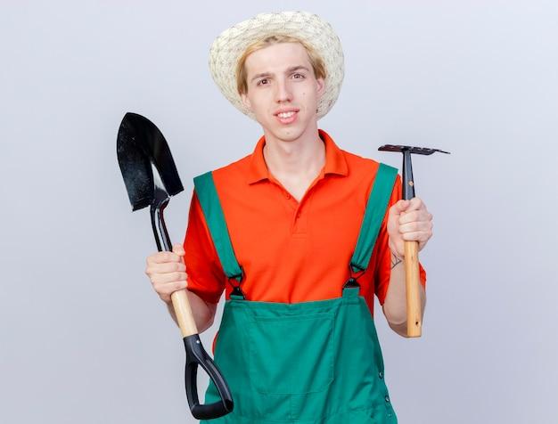 Jonge tuinman man dragen jumpsuit en hoed met mini hark en schop camera kijken met glimlach op gezicht blij en positief staande op witte achtergrond