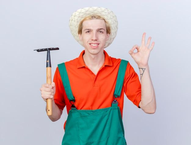 Jonge tuinman man dragen jumpsuit en hoed met mini hark kijken camera glimlachend vrolijk blij en positief weergegeven: ok teken staande op witte achtergrond