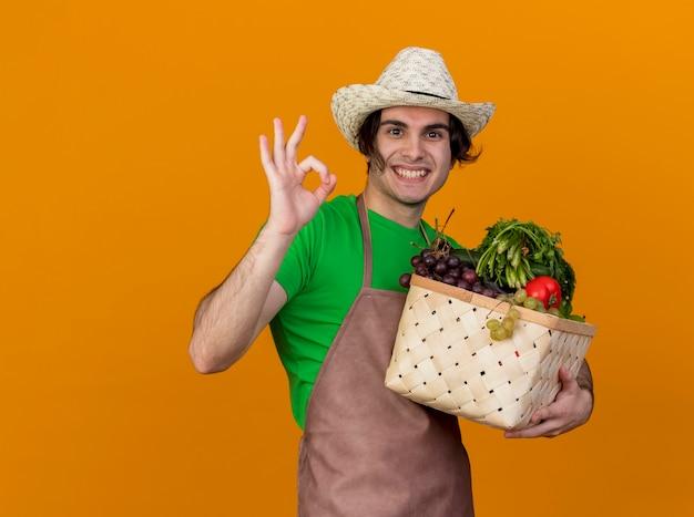Jonge tuinman man in schort en hoed bedrijf krat vol groenten kijken glimlachend vrolijk tonen ok teken staande over oranje muur