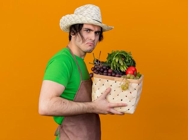Jonge tuinman man in schort en hoed bedrijf krat vol groenten kijken ontevreden fronsend staande over oranje muur