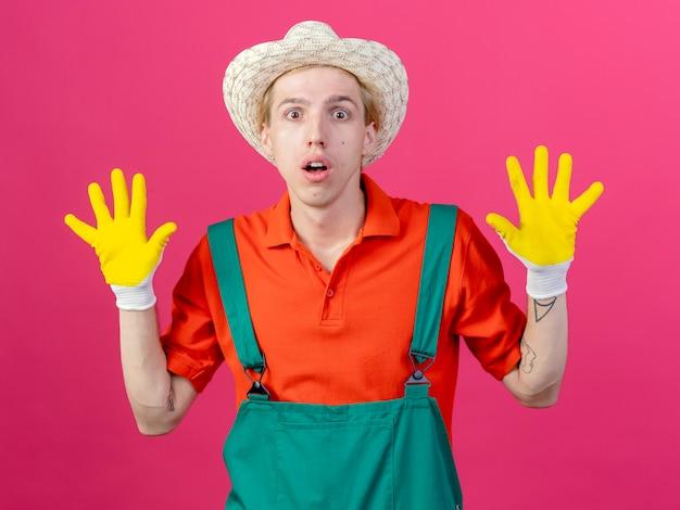Jonge tuinman man met jumpsuit en hoed in rubberen handschoenen handen opheffen
