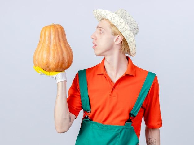 Jonge tuinman man met jumpsuit en hoed in rubberen handschoenen houden pompoen kijken geïntrigeerd staande op witte achtergrond