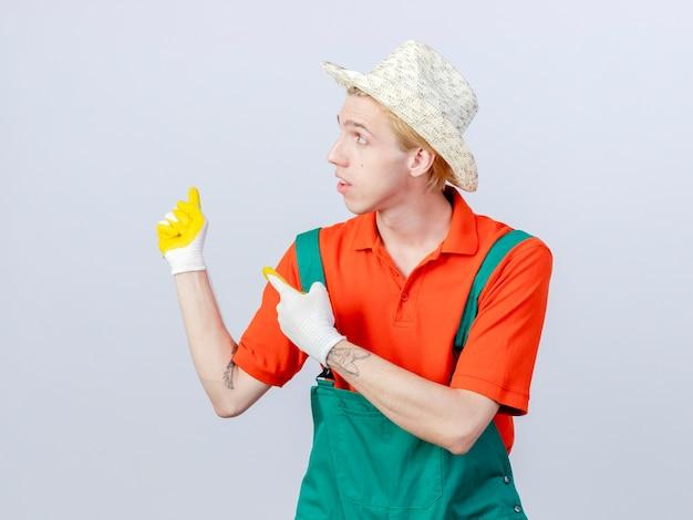 Jonge tuinman man met jumpsuit en hoed in rubberen handschoenen wijzend met wijsvinger naar de zijkant