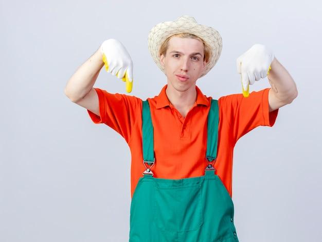 Jonge tuinman man met jumpsuit en hoed in rubberen handschoenen wijzend met wijsvingers naar beneden kijken zelfverzekerd staande op witte achtergrond