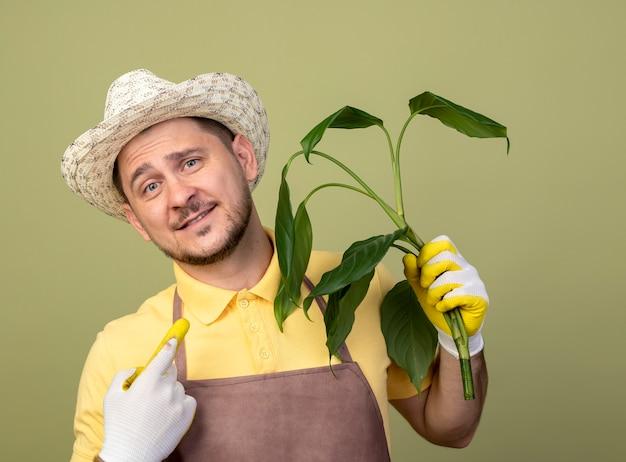 Jonge tuinman man met jumpsuit en hoed in werkhandschoenen bedrijf plant kijken voorkant lachend met blij gezicht staande over lichte muur