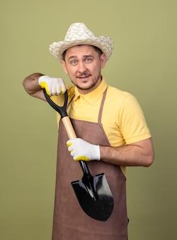 Jonge tuinman man met jumpsuit en hoed in werkhandschoenen houden schop kijken voorkant met glimlach op gezicht staande over lichte muur